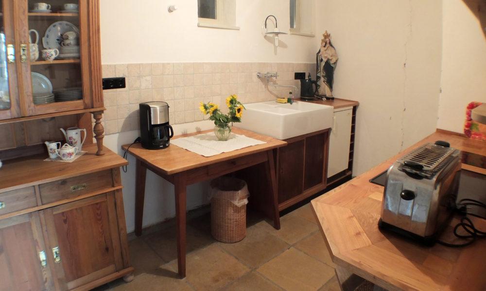 Von der Küche aus wird der Kachel im Wohnzimmer geschürt.